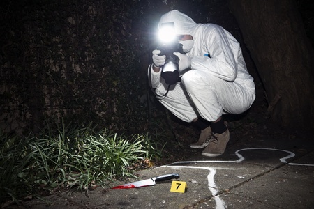 scene of the crime: Forensics researcher photographing a blood stained knife at a murder scene