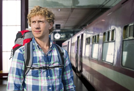 embark: Young man with a backpack ready to embark on a journey by train