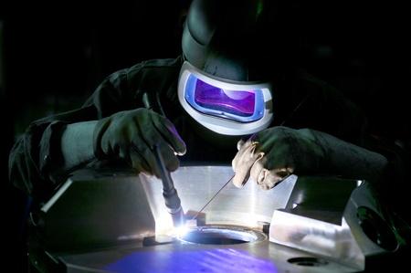 Lasser, werken op de middelste ring van een grote metalen deel Stockfoto