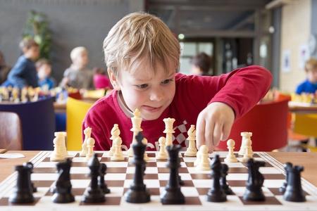 jugando ajedrez: Niño joven que hace un movimiento con un caballo durante un torneo de ajedrez en la escuela, con otros competidores en el fondo Foto de archivo