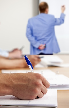 taking note: L'uomo, prendere appunti in una classe durante l'officina, scritto da un insegnante su una lavagna