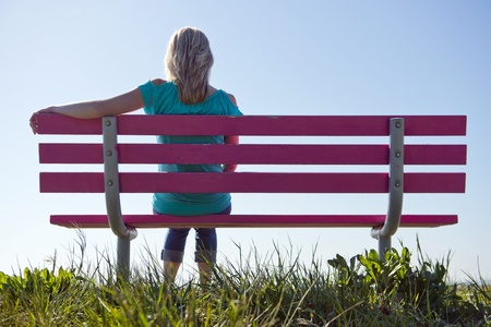 Young, blonde, woman sitting alone on a bench enjoying the warmth of the spring sun photo