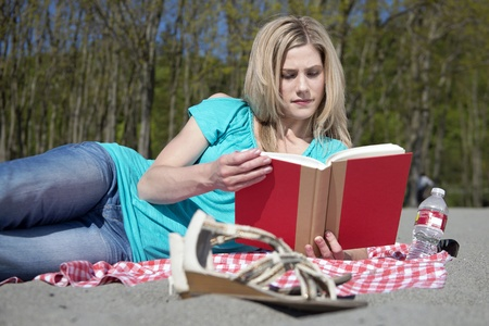 sandal tree: Attractive blonde woman reading a book on a sandy beach on a beautiful, sunny, spring day.
