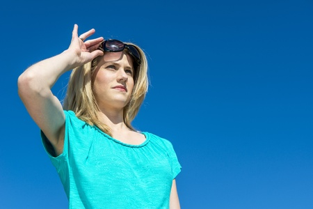 Attractive blonde woman, raising her sunglasses, against a bright blue sky on a beautiful warm spring day. photo
