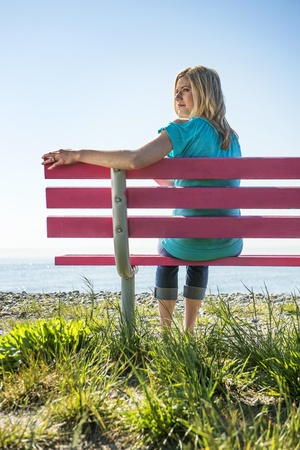 Attractive blonde woman wearing jeans and a turquoise top, sitting on a pink bench, overlooking the pacific ocean, looking over her shoulder photo