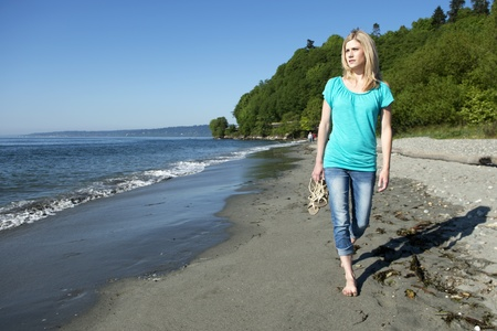 carying: Pretty young blonde woman walking barefoot over a beach through the wet sand