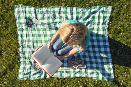Young Woman Sitting On Blanket Reading Book In Park, Seen from above photo