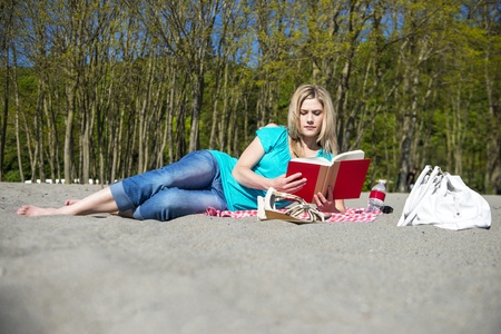 Young Woman Lying on her side in the Sand Reading Book At Beach photo