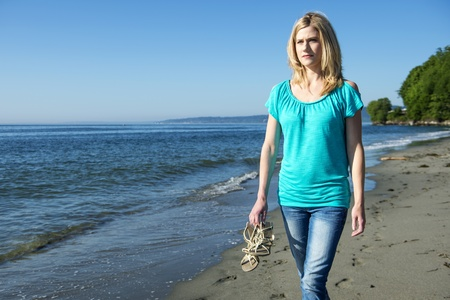 sandal tree: Young Woman Walking At Seashore Holding her sandals In her Hand Stock Photo