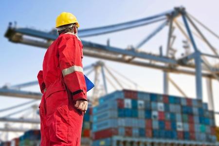 Konzeptionelle Bild der internationalen Logistik, die ein Hafenarbeiter, Blick auf die Entladung von einem Containerschiff von riesigen Kränen in der Ferne Standard-Bild