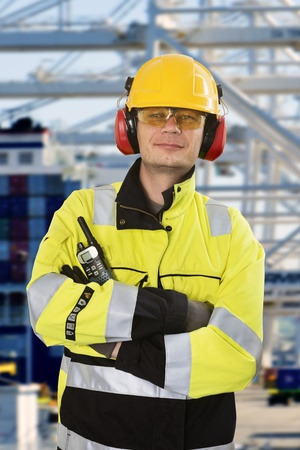 smirk: Portrait of a confident docker, wearing all required personal protective equipment, posing in front of an industrial container terminal and harbor