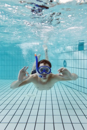excercise: Young male diver giving an ok hand signal, wearing a snorkle and diving glasses in an indoor swimming pool Stock Photo