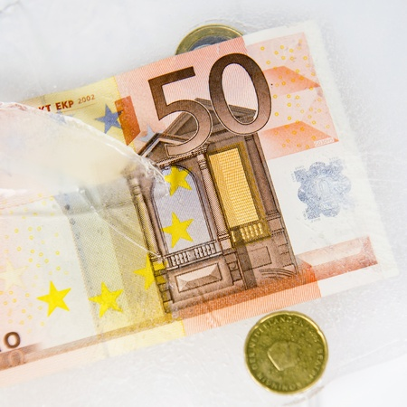 European currency, frosen in ice, as a concept for frozen assests, hidden costs, which reveal themselves as the ice melts - a metaphor for stronger regulations in the banking world photo