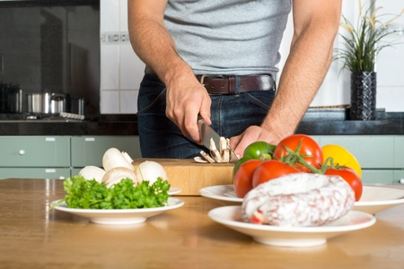 Midsection of young man cutting vegetables on wooden chopping board at kitchen counter Stock Photo - 21925079