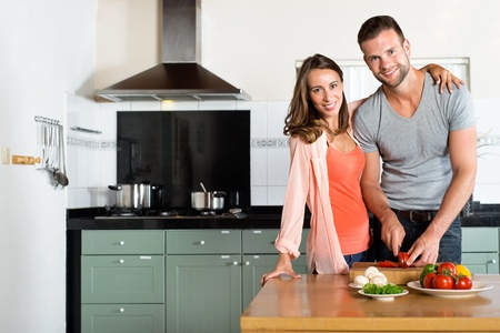 stove: Portrait of happy young couple cutting vegetables at kitchen counter Stock Photo