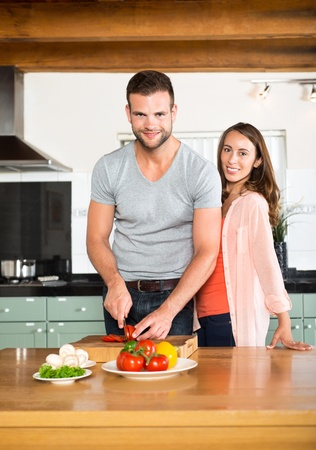 Portrait of happy young couple chopping vegetables at kitchen counter photo