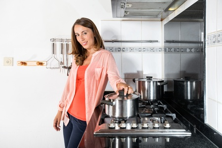gas stove: Portrait of beautiful young woman cooking food in domestic kitchen Stock Photo