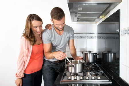 gas stove: Young couple cooking a meal on stove in domestic kitchen