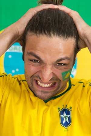 despondency: Despairing Brazilian sports fan, watching his national team fail in an important game