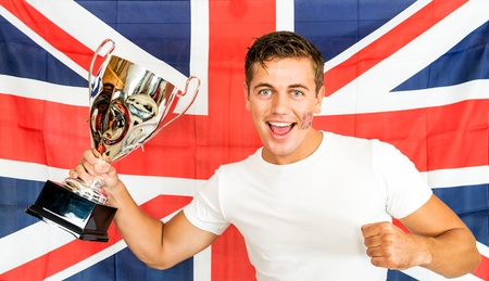 Portrait of successful sportsman holding trophy while standing against British flag photo