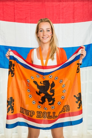 Portrait of happy young supporter of the Netherlands National theam, cheering and holding an orange flag while standing against the Dutch flag photo