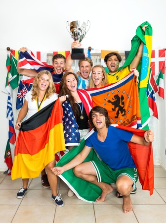 Group of young sports fans from various nations all over the world, celebrating and cheering together photo