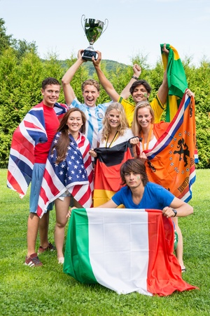 Group of international sports fans, each dressed in the color of their country and carrying the their nations flag winning the cup together. Sportivity, friendship and globalization theme photo