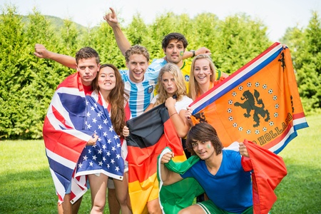 Group of international sports fans, each dressed in the color of their country and carrying the their nations flag. Sportivity, friendship and globalization theme photo