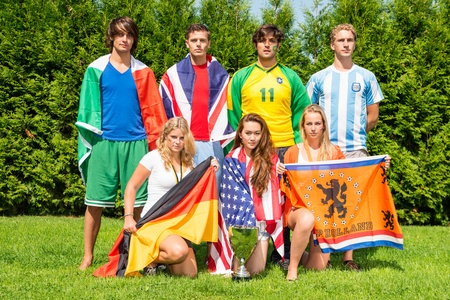 International sports team with men and women from various nationalities, each dressed in the color of their nation, holding their county's flags photo