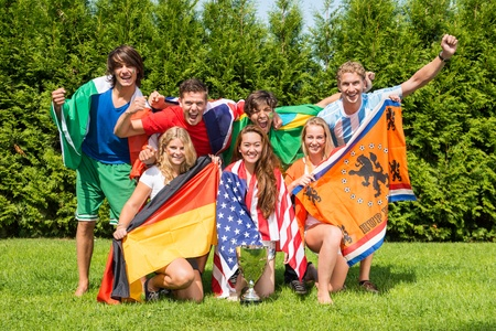 Portrait of cheerful young multiethnic athletes with various national flags celebrating in park photo