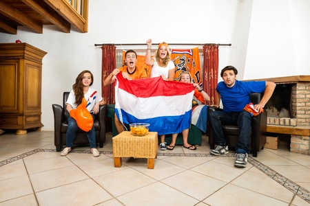 color fan: Group of young multiethnic soccer fans cheering while watching match at home