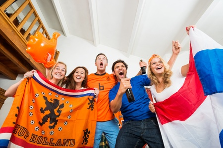 cheering fans: Excited young multiethnic soccer fans in Dutch national colors with tension and joy written on their faces, watching their national team perform well on television