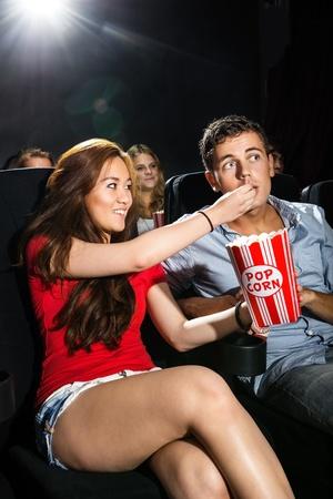 image date: Beautiful young woman feeding popcorn to boyfriend in cinema theatre
