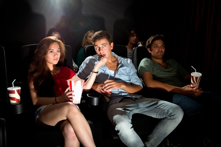 los jóvenes en una sala de cine viendo una película con atención, con palomitas y soda. Una mujer asiática que introduce a su novio palomitas Foto de archivo