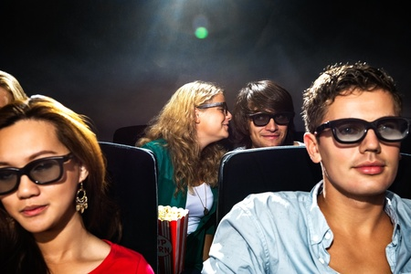 Young woman whispering in boyfriend's ear while watching movie in cinema theatre photo