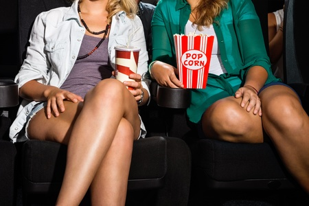 theater popcorn: Midsection of young women with popcorn and soda sitting in cinema theater