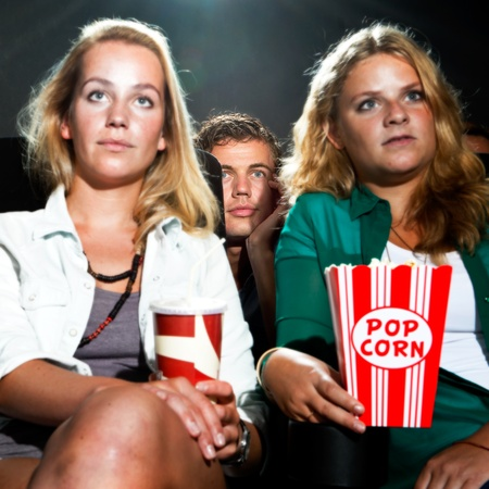 feature films: Man peeking between the two seats in front of him to get a better view of the movie on show Stock Photo