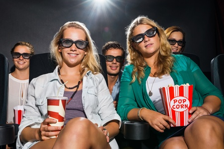 Portrait of happy young friends with popcorn and soda watching 3D movie in theater photo