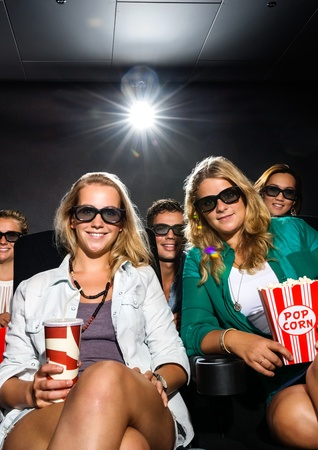 Group friends with snacks watching 3D movie in theater photo