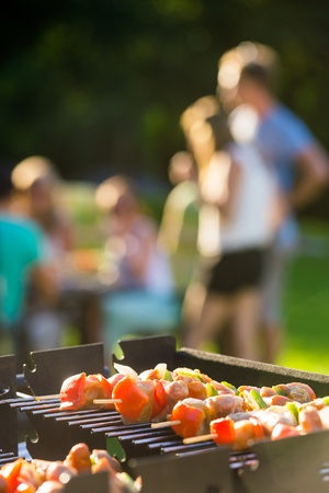 lawn party: Close-up of skewers grilling on barbecue at garden party Stock Photo
