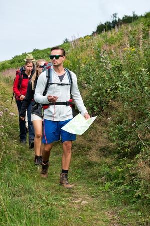 Eine Gruppe von Freunden mit Rucksäcken wandern in Graslandschaft