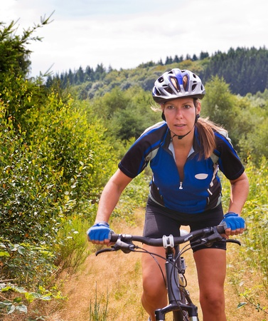 Woman standing on the pedals of her mountain bike, cycling uphill on a small trail photo