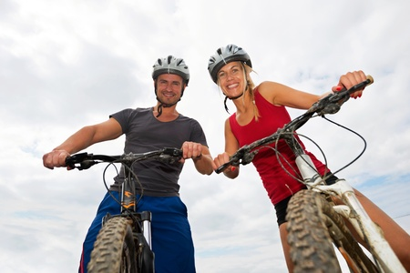 Portrait of a happy young couple on mountain bikes photo