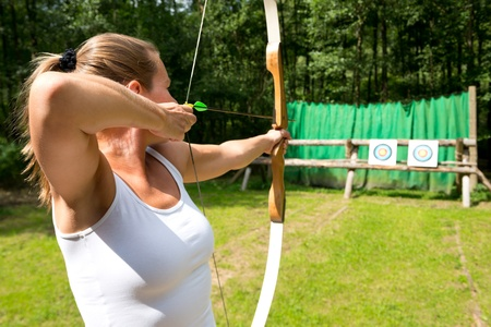 A female archer aiming at a target on a sunny day photo