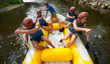 A group of friends in an inflatable raft moving down a river photo