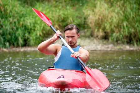 A young man kayaking down a river