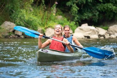 Zwei lächelnde junge Frauen Kajak auf einem Fluss