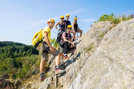 Group of climbers with safety equipment on rock photo