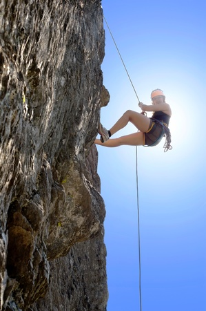 abseiling: Full length of young woman climbing rock Stock Photo