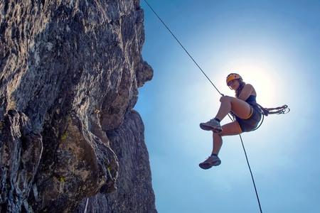 Jeune, dur, femme, descente en rappel à partir d'un rocher escarpé, juste en face du soleil